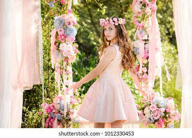 Beautiful girl in an amazing dress outdoors. Decoration with flowers.