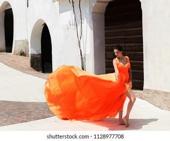 Beautiful girl in amazing fluttering orange dress.