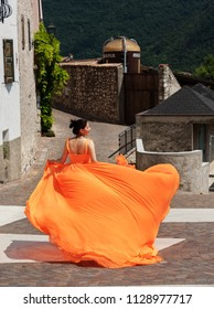 Beautiful girl in amazing fluttering orange dress running forward in old town.