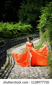 Beautiful girl in amazing fluttering orange dress standing on the cobblestone curved road.