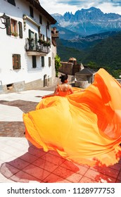 Beautiful girl in amazing fluttering orange dress running forward in old town. With mountais on background.