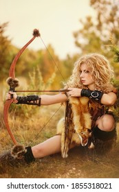 Beautiful girl- amazon with bow in hands in autumn time at the big mountain