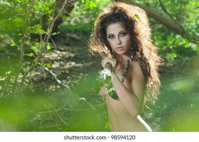 The beautiful girl amazon poses in jungle with a spear