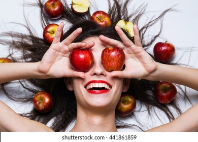 A beautiful girl with apples. lying on a white background