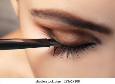 Beautiful girl applying cosmetics, closeup