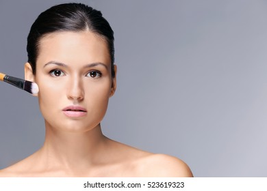 Beautiful girl applying cosmetics on grey background