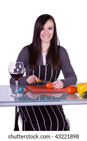 Beautiful Girl with an Apron Preparing Food and Drinking Wine