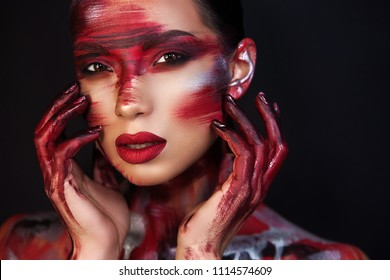a beautiful girl with Asian roots on a black background holds her hands in the face which are covered with an original makeup with a red train.