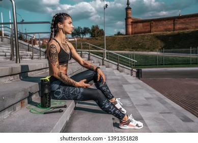 Beautiful girl athlete in tattoos, summer city, resting after fitness workout. Sportswear leggings top. Shaker with water protein skipping, rope smartphone headphones. Free space. Listening music.