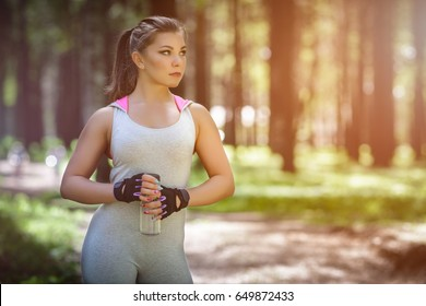 Beautiful girl athletic build in gray sports suit. on a run in the park, with a bottle of water