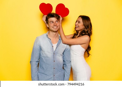 Beautiful girl and attractive celebrating St. Valentine's day, have fun together, joking, playing with hearts attributes. Dressed in jeans shirt and white dress.