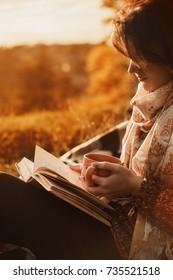 Menina bonita na floresta de outono lendo um livro coberto com um cobertor quente.uma mulher se senta perto de uma árvore em uma floresta de outono e segura um livro e uma xícara com uma bebida quente em suas mãos. Menina lendo um livro