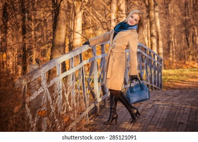 Beautiful girl in the autumn park near the water