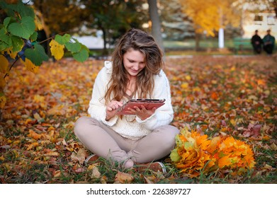 beautiful girl in autumn park with a tablet resting.