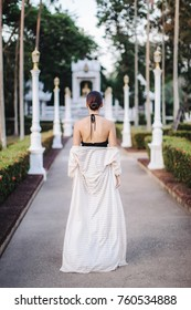 beautiful girl from the back, leaves in a beautiful white temple