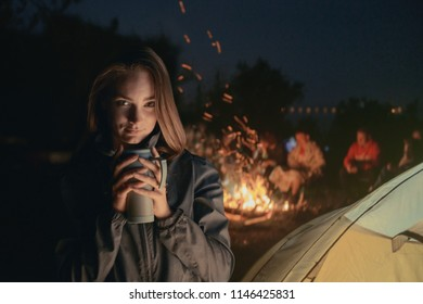 Beautiful girl in the background of a campfire with a cup of hot drink.