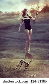 beautiful girl balances on back of chair outdoors. Artwork