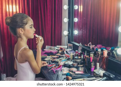 Beautiful girl, a ballet dancer Looking at the mirror and lipstick makeup behind the stage before starting acting