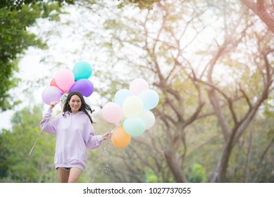 beautiful girl with balloons in park