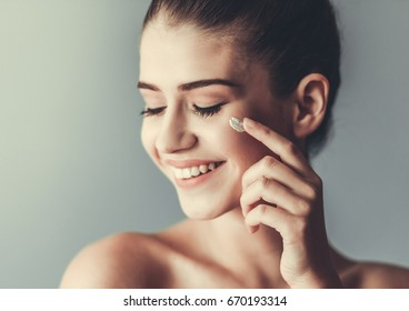 Beautiful girl with bare shoulders is applying cream on her face and smiling, on gray background
