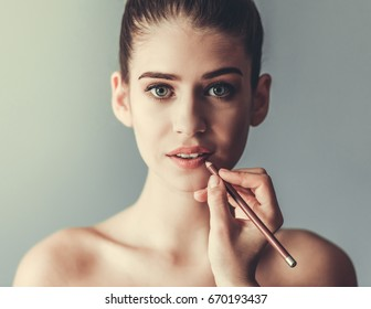 Beautiful girl with bare shoulders is looking at camera while having her lips made with lip pencil, on gray background