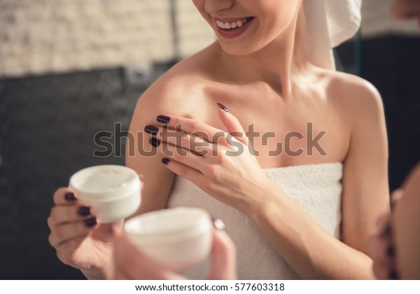 Beautiful girl in bath towel is applying cream on her shoulder while standing in front of the mirror in bathroom