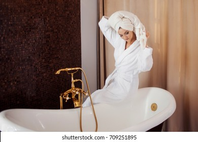 Beautiful girl in a Bathrobe drying her hair with a towel. Girl after bath
