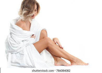 Beautiful girl in bathrobe is touching her legs. Spa, depilation and bodycare concept