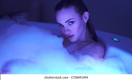 Beautiful girl in the bathroom with foam looking at the camera