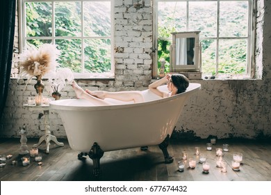 Beautiful girl in a bathtub with candles in glasses on the floor and fluffy feathers on a white table