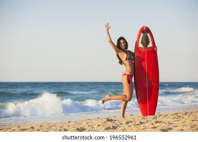 A beautiful girl at the beach holding her surfboard