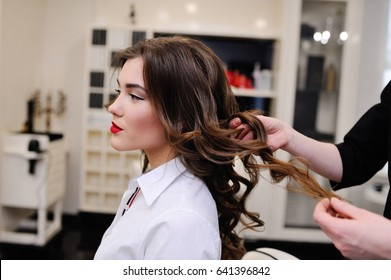 Beautiful girl in the beauty salon makes a chic hairstyle