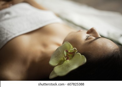 beautiful girl in a beauty salon with orchid flower in her hair. spa treatments. close-up