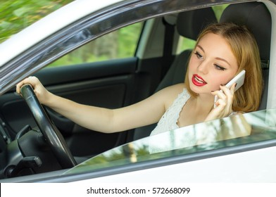 Beautiful girl behind the wheel of a car talking on the phone, watch in the rear view mirror