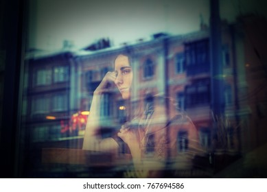 Beautiful girl behind the window. She is sitting in a nice cafe and looking through glass. City street is reflected in the window. It is evening time.
