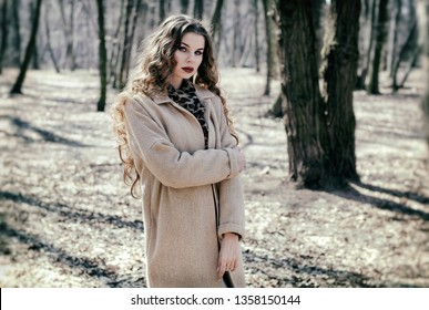 Beautiful girl in beige coat walkin in the park. Image with vintage film camera effects