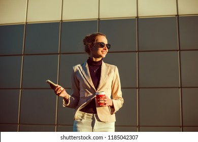A beautiful girl in a beige jacket drinks coffee from a glass talking on the phone, wearing sunglasses works in the office in the business center, the manager, the employee of the company, happy face