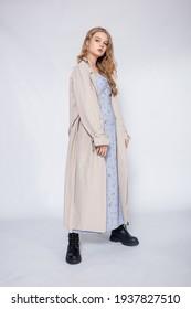 beautiful girl in beige raincoat posing in Studio on grey background
