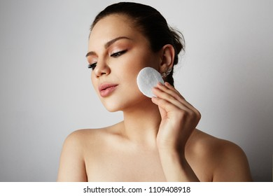 Beautiful girl with big brown eyes and dark eyebrows refreshing skin face with cotton pads over gray studio background.Model with light nude make-up.Healthcare skin makeup concept