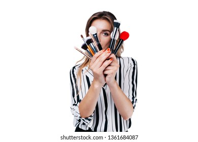 beautiful girl with big eyes, professional make-up artist in a striped shirt on a white background looks through the tassels with his eye into the camera