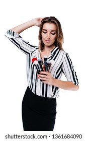 beautiful girl with big eyes, professional makeup artist in a striped shirt on a white background looks at the tassels