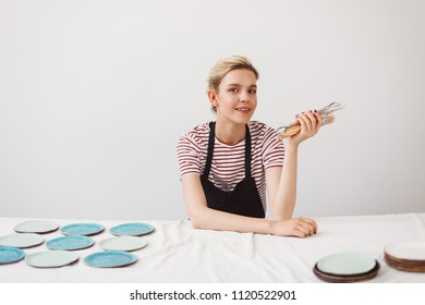 Beautiful girl in black apron and striped T-shirt sitting at the table with plates and holding pottery tools in hand dreamily looking in camera at pottery studio