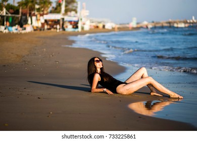 Beautiful girl in a black body by the sea