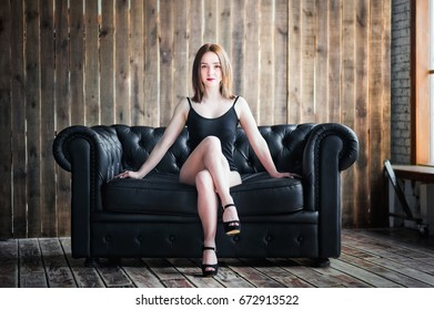 Beautiful girl in black body, A girl is sitting on a black leather couch. A girl with red lipstick posing in front of the camera. Girl of athletic appearance on a background of a wooden wall
