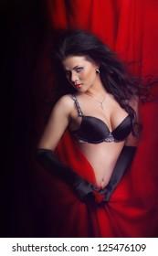 beautiful girl in black bra on the red sheet