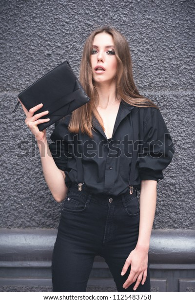 Beautiful girl with a black clutch in her hand. Woman in dark clothes on a dark background in the street. Toned image.
