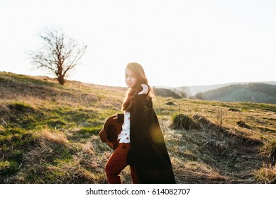 Beautiful girl in a black coat, brown pants and with a hat walks to mountain places with a young spring grass. traveler hipster holding hat in sunset. Wearing stylish fall outfit