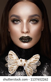 Beautiful girl with black creative art make-up and gold accessories. Beauty face. Photos shot in studio