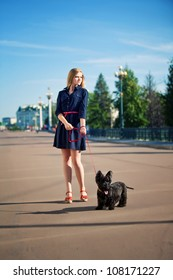 beautiful girl with a black dog on the background of the bridge in the park