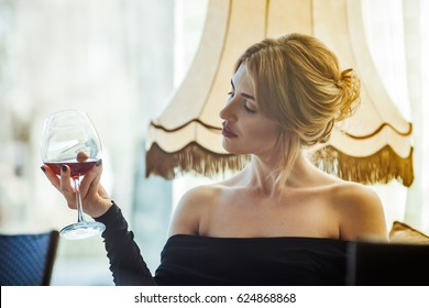 The beautiful girl in a black dress drinks wine at restaurant. She gently holds a glass in the hand and looks at it. The girl's ringlets tremblingly iron her face.